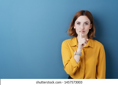 Attractive young woman making a shushing gesture with her finger to her lips as she asks for silence or to keep a secret over blue with copy space