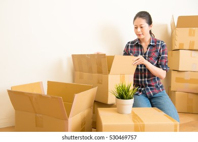 Attractive young woman is moving, standing among cardboard boxes. mixed race asian chinese model