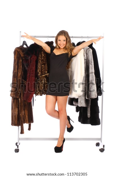Attractive young woman near the hanger with a fur coats on white background