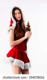 Attractive young woman with New Year tree in Santa costume.