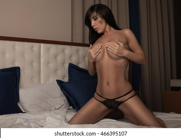 Attractive young woman on a bed in black intimate underwear