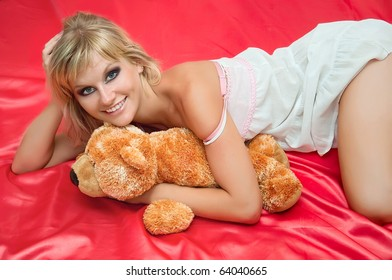 attractive young woman on a bed on pink with toy