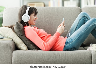 Attractive young woman on the sofa at home, she is playing music with her smarphone and wearing headphones, leisure and entertainment concept