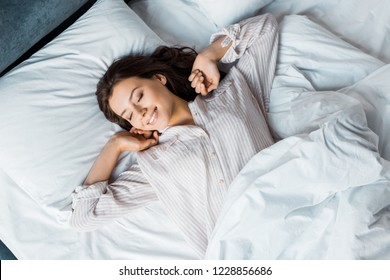 attractive young woman in pajamas waking up in bed in the morning