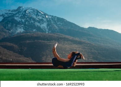 Attractive young woman performing yoga on the green lawn and reading a book in a funny position with legs over her head with great mountain view background