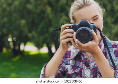 Attractive young woman photographing with professional camera outdoors, copy space. Taking photos and photography classes concept