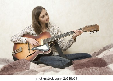 Attractive young woman playing guitar sitting on bed