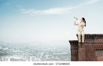 Attractive young woman playing music on roof of building. Brave businesswoman in white business suit with trumpet instrument sitting on edge of roof. Music performance on roof in modern city.