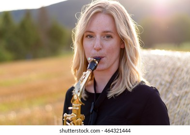 Attractive young woman playing a tenor saxophone as she stands outdoors in an agricultural field in front of a hay bale, with sun flare