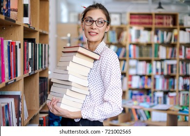 Attractive young woman portrait wearing pink pale shirt with dots and fashionable glasses holding a stack of books in the library surrounded by bookshelves with colorful books.