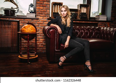 Attractive young woman posing on a leather sofa in a room with brick walls. Loft style interior. Beauty, fashion. Evening makeup and hairstyle.