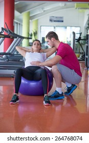 attractive young woman practicing on the exercise ball with her fitness trainer at the gym