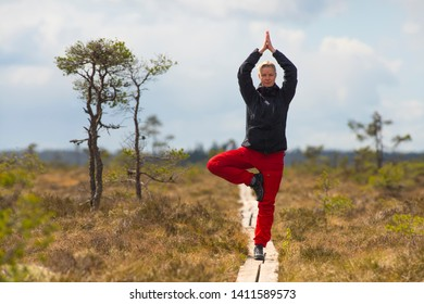 Attractive Young Woman practicing Yoga standing tree pose (Vrikshasana) with hands over head - Outdoor in nature with wildlife clothing in wide open landscape background - Horizontal photograph.