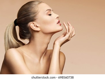 Attractive young woman in profile touching her lips. Photo of sensual woman with fresh makeup on beige background. Youth and skin care concept