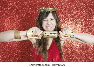 Attractive young woman pulling a Christmas cracker open while standing on a red glitter background.