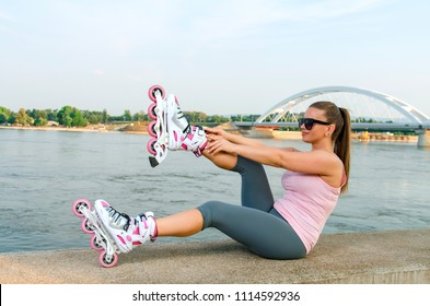Attractive young woman putting on roller skates , outdoors