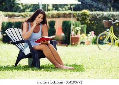 Attractive young woman reading a book in the garden