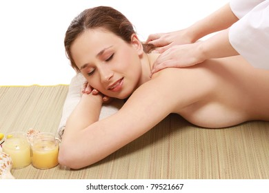 An attractive young woman receiving massage, isolated on white