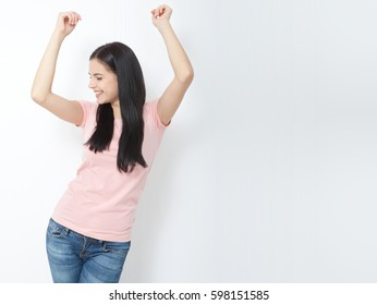Attractive young woman relax and dance on copy space. Portrait of happy girl dancing your hands up on white background