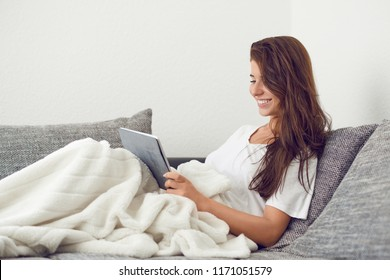 Attractive young woman relaxing at home on a couch with a rug over her knees and tablet computer looking at the camera with a warm friendly smile
