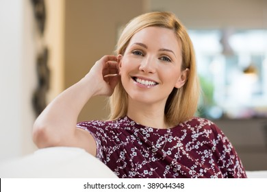 Attractive young woman relaxing at home. Smiling young woman sitting in sofa at home and looking at camera. Portrait of happy girl at home.