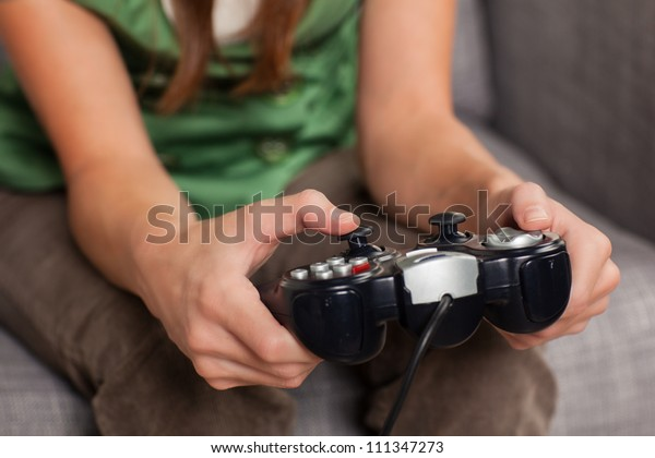 Attractive young woman relaxing at home playing a game holding controller sitting on couch.