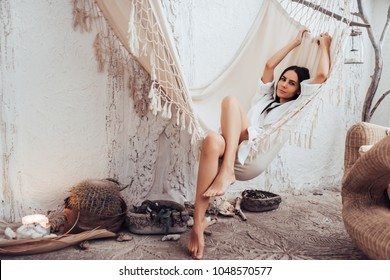 Attractive young woman is relaxing in spa and wellness center while lying in hammock. Beauty treatment concept.