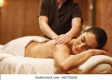 Attractive young woman relaxing at spa center receiving back massage by a professional masseur copyspace relaxation recreation luxury hotel resort wellness beauty body care therapy health enjoyment
