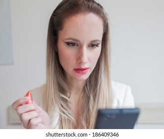 Attractive young woman in the restaurant holding lipstick and looking at her phone.