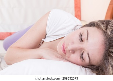 Attractive young woman resting peacefully on her side