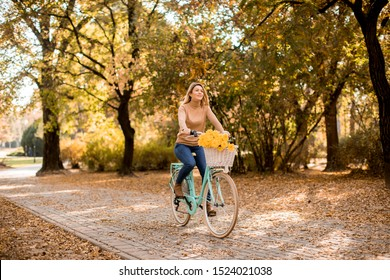 Attractive young woman riding bicycle in golden autumn park