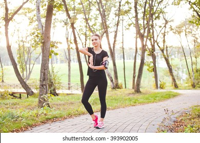 Attractive young woman runner athlete touch her phone in armband during training in evening park on a path with earphones at sunset. Adjust and look at gadget display before run. Full length portrait