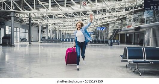 Attractive young woman is running in airport terminal with pink suitcase. Ready for traveling!