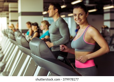 Attractive young woman running on a treadmill in gym, looking at camera and smiling