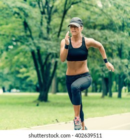 Attractive young woman running in park. Wearing modern black sport outfit. Toned image