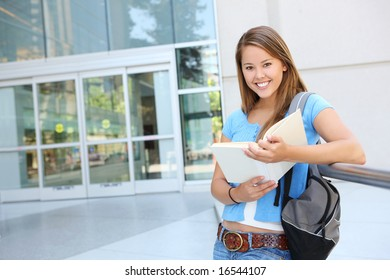 Attractive young woman at school library holding book