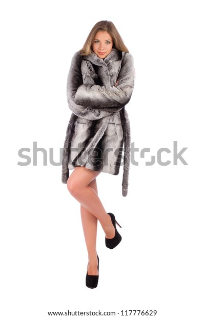 Attractive young woman shaking trying to warm on fur coat isolated on white background