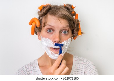 Attractive young woman shaves her face with foam and razor