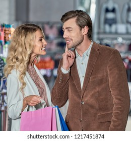 attractive young woman with shopping bags able to kiss smiling man in store