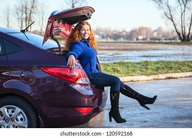 Attractive young woman sitting in car luggage trunk