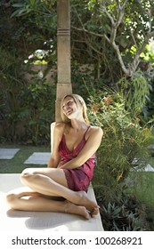 Attractive young woman sitting down in a tropical garden on a summer sunny day, laughing.