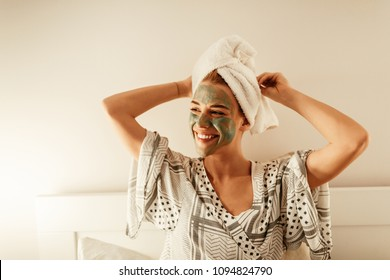 Attractive young woman sitting with a facial mask on her skin