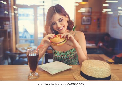 Attractive young woman sitting indoor in urban cafe. Cafe city lifestyle. Casual portrait of teenager girl. Toned.
