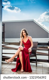 Attractive young woman, sitting with legs crossed, outdoor on a bright sunny day in  long red dress, looking at camera