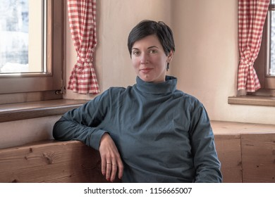 Attractive young woman sitting in mountain cabin next to the window in winter time during ski break