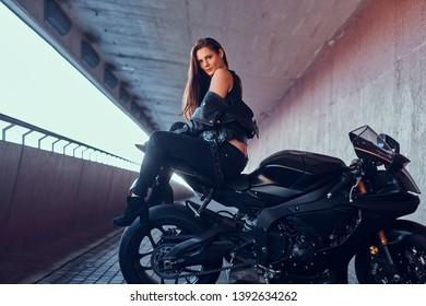 Attractive young woman is sitting on her motobike in tunnel.