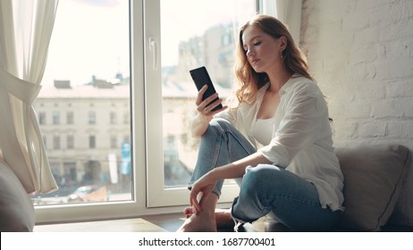Attractive young woman sitting on a windowsill at home and texting on her phone communication female looking message cellphone cheerful smile use internet modern smartphone