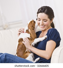 An attractive young woman sitting on a couch and being kissed by a dog that she is holding.  She is smiling and her eyes are closed. Square framed photo.