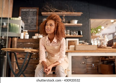 Attractive young woman sitting on a chair while working in a cafe