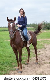 Attractive young woman sitting on chestnut horse while riding on field